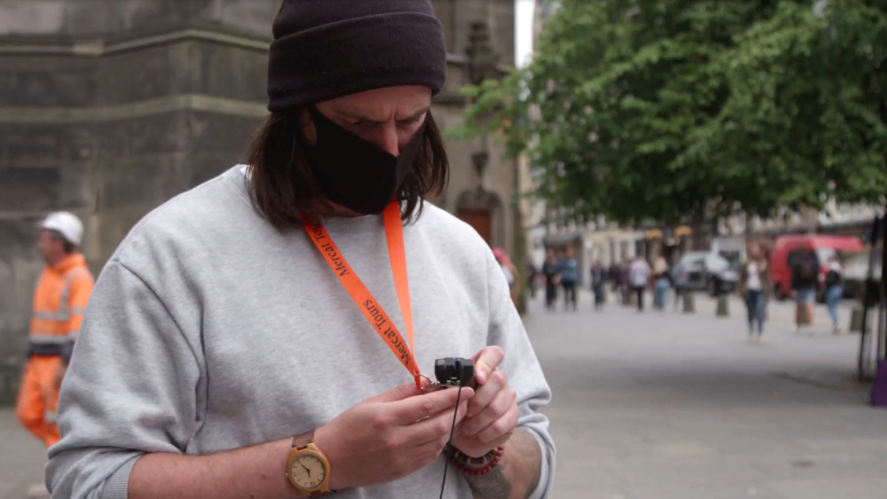 Tourist using a tour guide system wearing a face mask in city centre